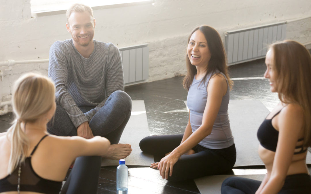 Group of fit happy people sitting on mats in fitness studio room chatting, joking, laughing together, talking in a circle after practice.