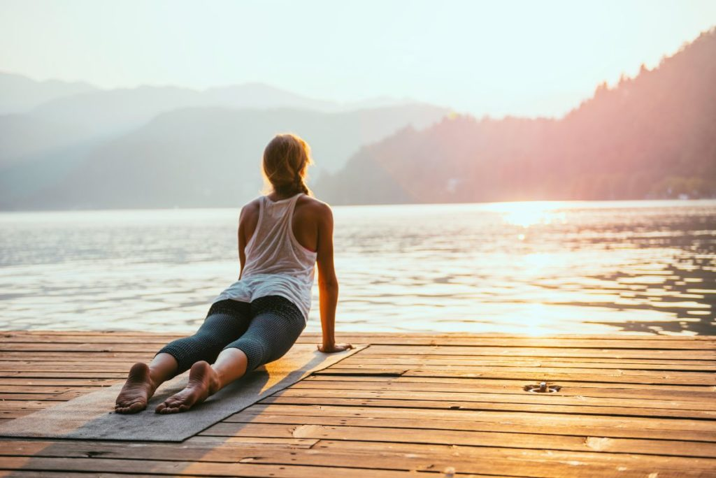 Woman doing yoga in nature by the lake