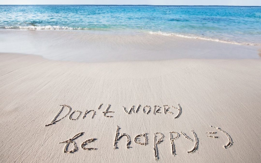 Dont worry be happy written on beach with a smile
