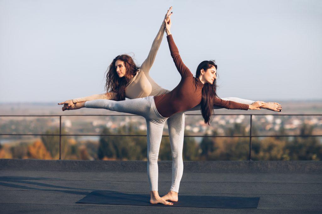 Two young beautiful women doing yoga asana virabhadrasana helping each other on the roof outdoor. partner yoga.