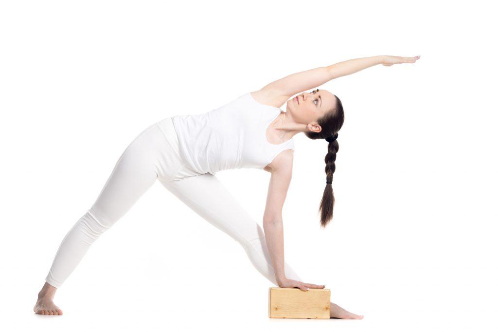 Sporty beautiful young beginning yoga female student standing in Utthita Trikonasana, Extended Triangle Pose leaning on yogic wood brick, studio full length profile view on white background, isolated