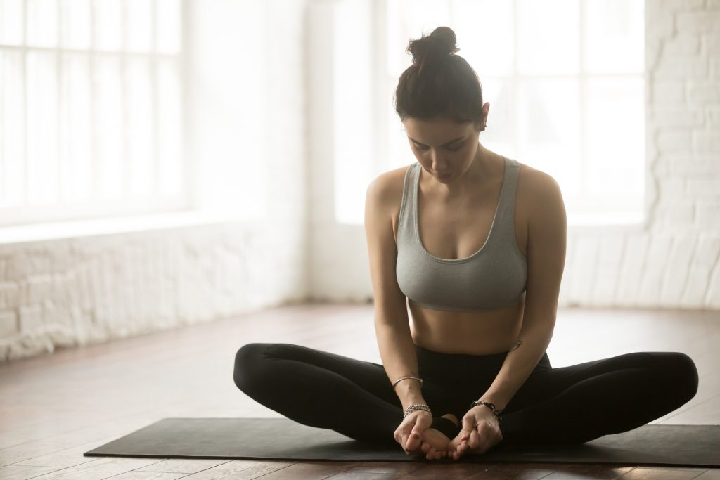 Young attractive sporty yogi woman practicing yoga concept, sitting in baddha konasana exercise, Butterfly pose, working out wearing sportswear bra and pants, full length, white loft studio background