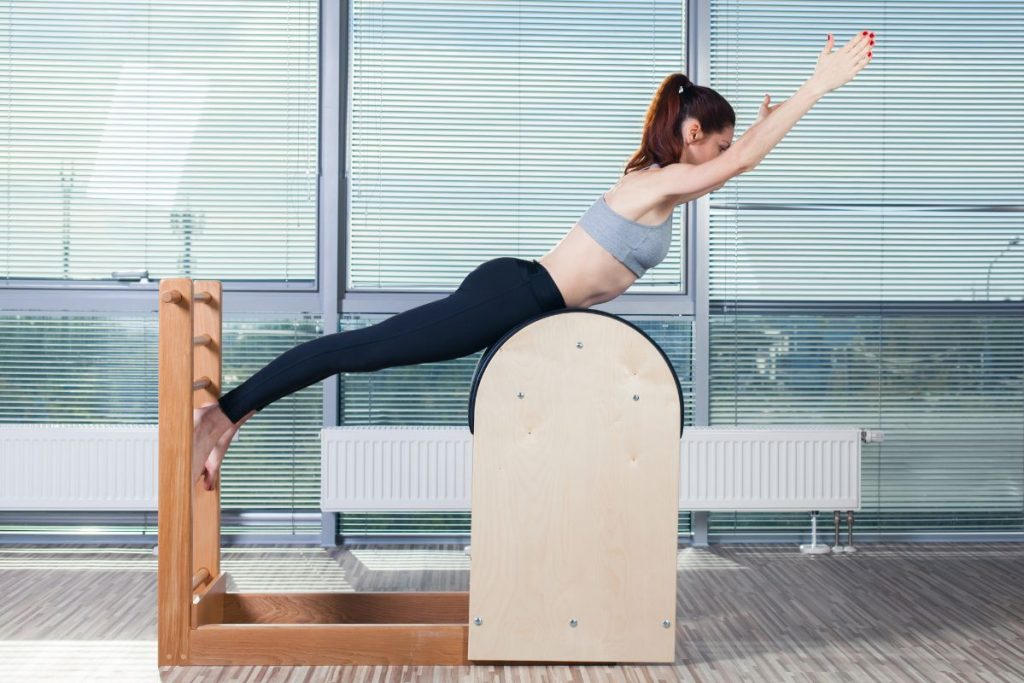 Woman doing pilates on ladder barrel