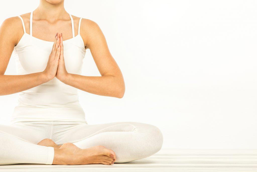 Woman sitting in lotus position doing namaste