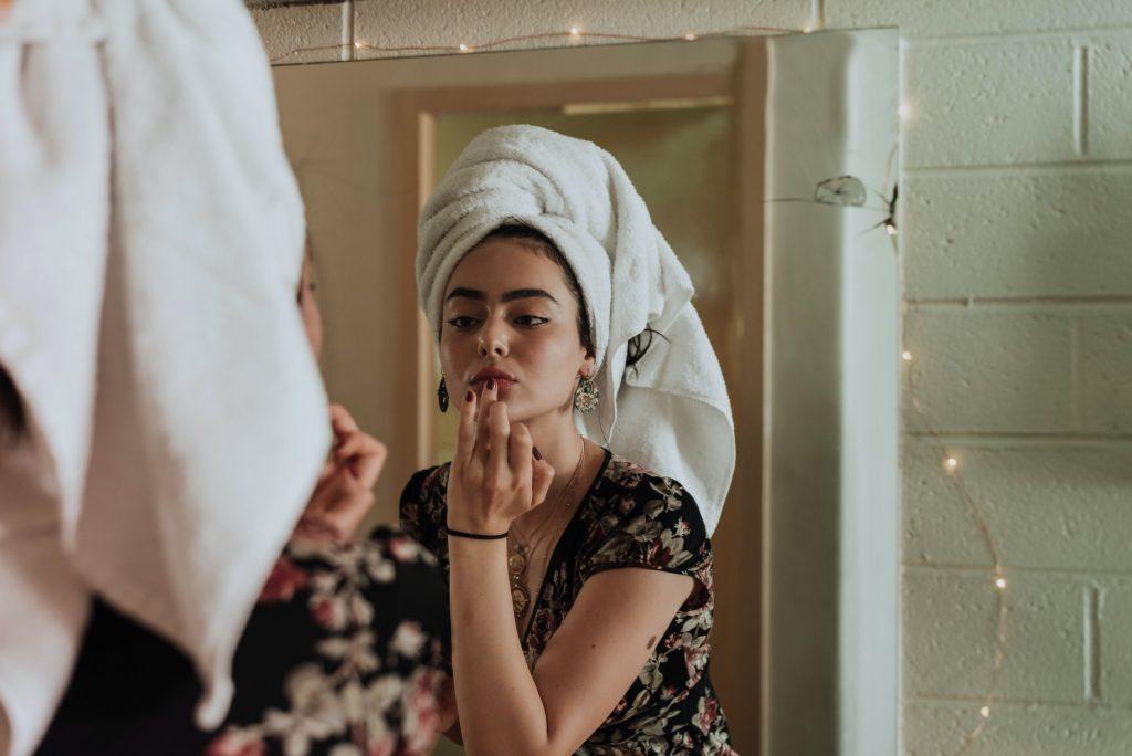 woman doing make up mirror