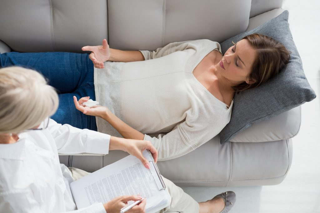 High angle view of woman lying on sofa by her therapist at home