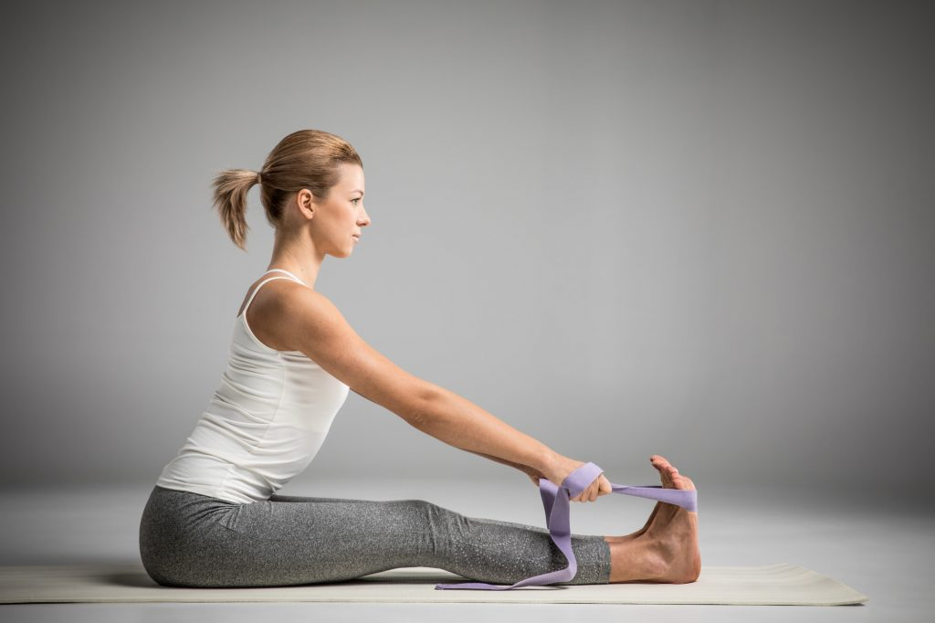 Woman yoga pose seated forward bend assisted with a strap