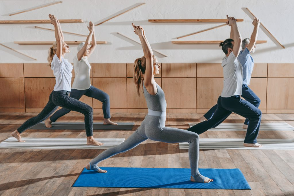 Group of people practicing yoga with instructor in warrior pose on mats in studio