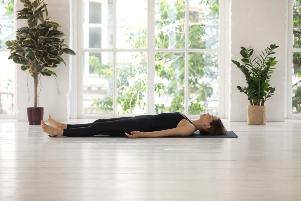 Young woman wearing black sportswear doing Savasana exercise, relaxing in Dead Body, Corpse pose, practicing yoga, beautiful sporty girl working out at home or in yoga studio with window and plants