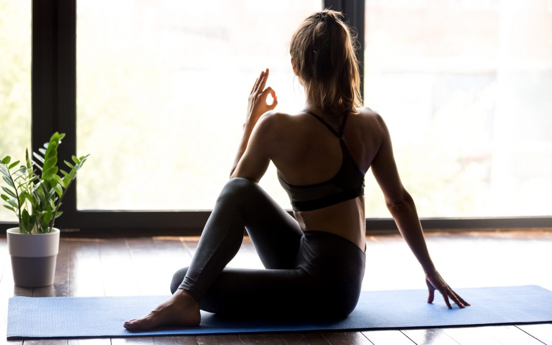 Young sporty woman in Ardha Matsyendrasana yoga pose