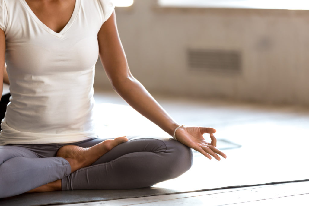 Young yogi woman practicing yoga, doing Ardha Padmasana exercise, Half Lotus pose with mudra gesture, working out, wearing sportswear, indoor close up, yoga studio. Well being, wellness concept
