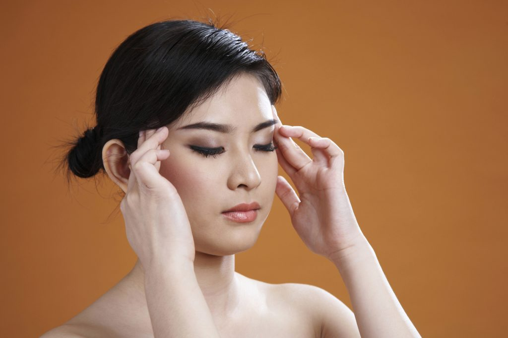 young asian woman with her fingers on her temples
