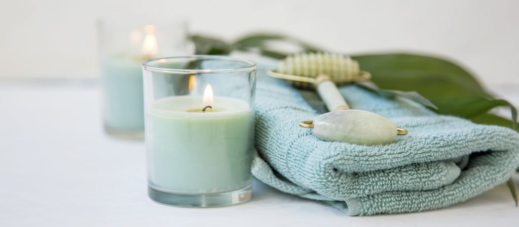 Spa still life with jade roller, candles, towels and green leaf plant , spa and wellness setting