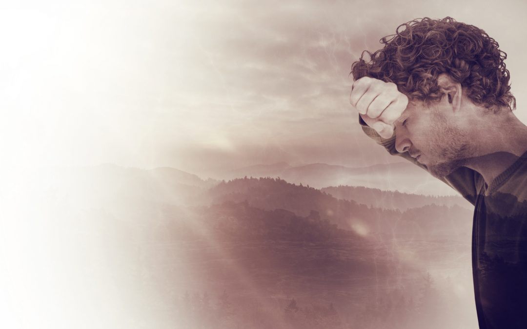 Depressed man over white background against trees and mountain range against cloudy sky