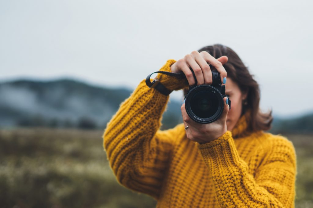 photographer girl hold in hands video camera take photo on background autumn foggy mountain, tourist shooting nature mist landscape, photo lens closeup