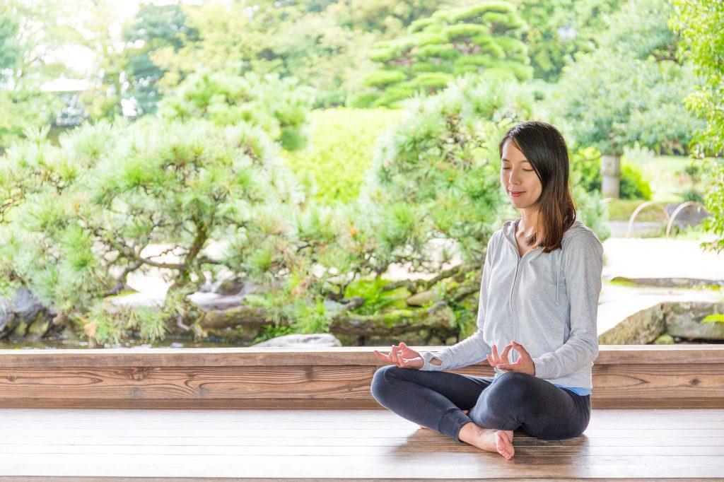 Woman enjoying her meditation in a garden
